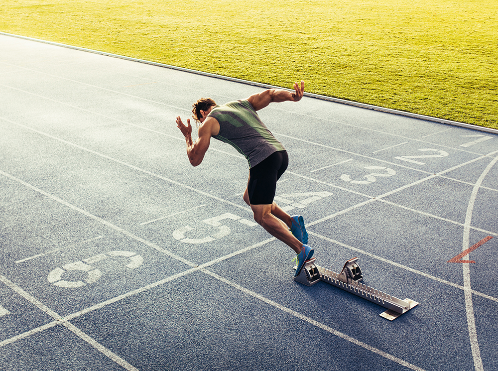 Athlete sprinting off of a starting block.